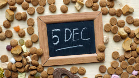 festiveness: 5th of December in Dutch written on a chalkboard between ginger nuts and candys for the Dutch Santa-Claus celebration of the 5th of December