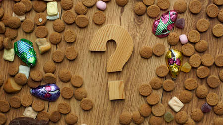 ginger nuts: Wooden question mark between ginger nuts and candys for the Dutch Santa-Claus celebration of the 5th of December