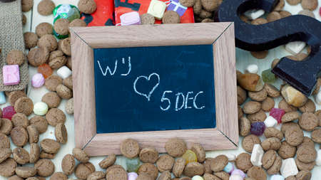 festiveness: We love 5th of December in Dutch written on a chalkboard between ginger nuts and candys for the Dutch Santa-Claus celebration of the 5th of December