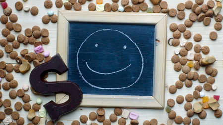 nicolaas: A smile painted on a chalkboard between ginger nuts and candys for the Dutch Santa-Claus celebration of the 5th of December