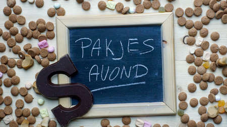 festiveness: Present evening in Dutch written on a chalkboard between ginger nuts and candys for the Dutch Santa-Claus celebration of the 5th of December