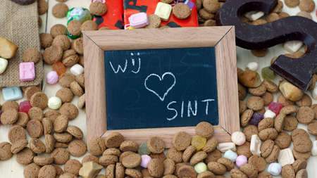 sinterklaasfeest: We love Santa-Claus in Dutch written on a chalkboard between ginger nuts and candys for the Dutch Santa-Claus celebration of the 5th of December