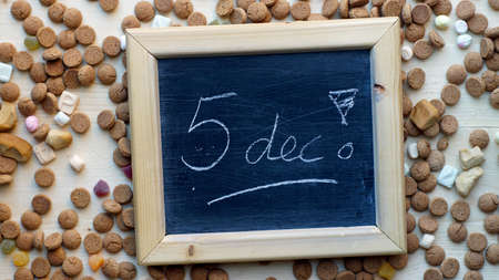 festiveness: 5th december in Dutch written on a chalkboard between ginger nuts and candys for the Dutch Santa-Claus celebration of the 5th of December