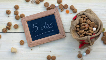 ginger nuts: 5th december in Dutch written on a chalkboard between ginger nuts and candys for the Dutch Santa-Claus celebration of the 5th of December