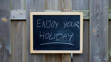 stay in the green: Enjoy your holiday written on a chalkboard hanging in the garden