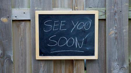 See you soon written on a chalkboard in the garden Standard-Bild