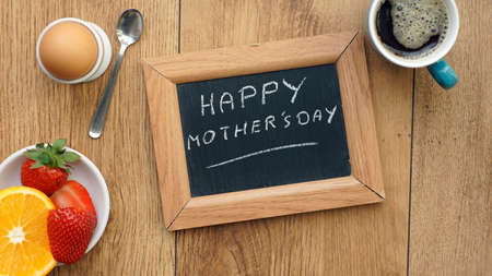 Mother's day written on a chalkboard between a breakfast for her