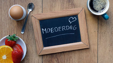 Mother's day written in Dutch on a chalkboard between a breakfast for her