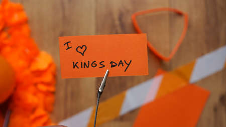I love Kingsday in Dutch written on a card at a table with orange stuff for Kingsday