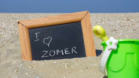 beach access: I love the summer written in Dutch on a chalkboard at the beach in front of the sea