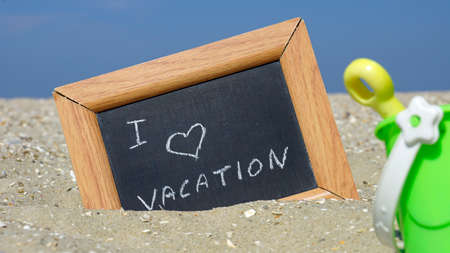 beach access: I love vacation written on a chalkboard at the beach