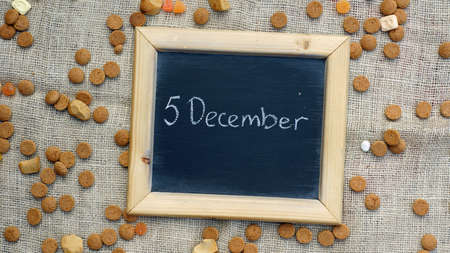 ginger nuts: 5th of December in Dutch written on a chalkboard between ginger nuts and candys for the Dutch Santa-Claus