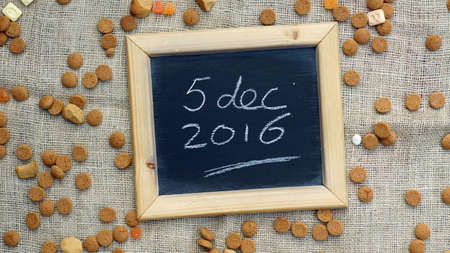 festiveness: 5th of December 2016 in Dutch written on a chalkboard between ginger nuts and candys for the Dutch Santa-Claus