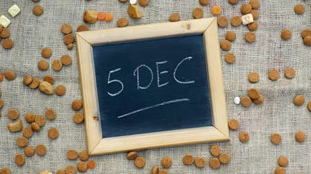 festiveness: 5th of December in Dutch written on a chalkboard between ginger nuts and candys for the Dutch Santa-Claus