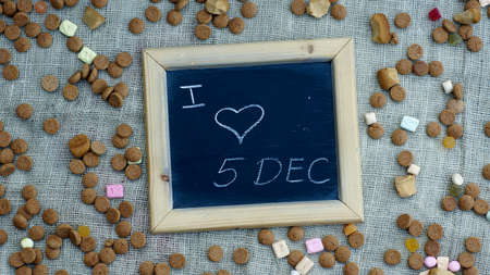 festiveness: I love the 5th of December in Dutch written on a chalkboard between ginger nuts and candys for the Dutch Santa-Claus Stock Photo