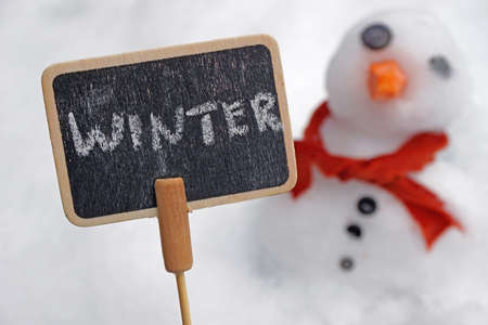 Winter written on a card with a snowman behind