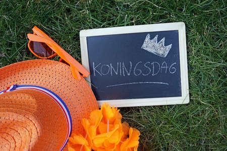 Kingsday written in Dutch on a chalkboard next to orange things