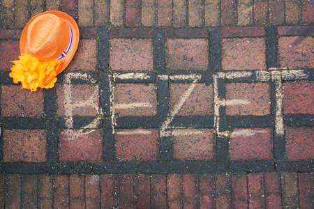 Bezet geschreven in het Nederlands op de straat voor Nederlandse koningsdag met een oranje kop