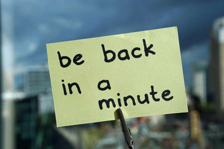 Seien Sie in einer Minute zurück, geschrieben auf einem Memo im Büro in der Stadt Standard-Bild - 107926280