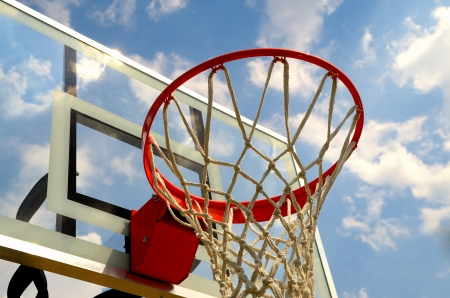 Bottom view of a basketball hoop with the backboard and sky in the background. Banco de Imagens
