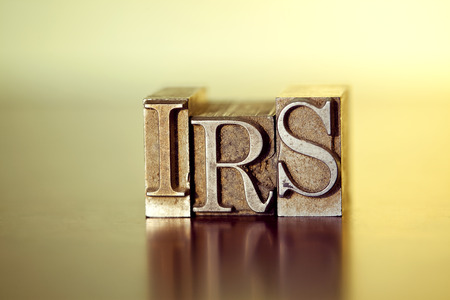 IRS spelled out in vintage letterpress blocks. Фото со стока