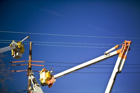 Electric utility work on a pole.