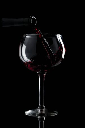 Red wine being poured into a wide glass Stock Photo