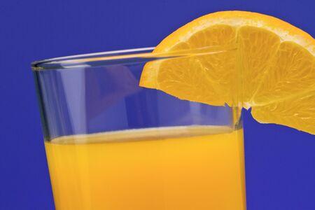 Glass of orange juice with an orange wedge.
