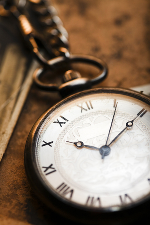 Old Fashioned Pocket Watch on a textured surface.