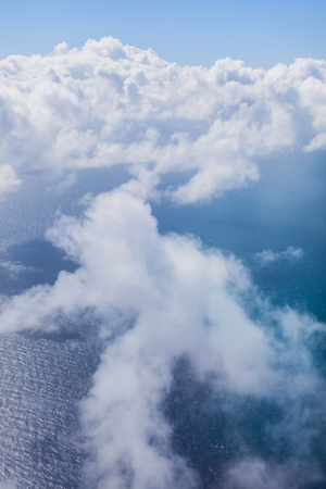 Flying over the Ocean with scattered clouds Stock Photo