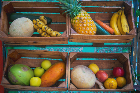 Mix of tropical and traditional fruits and vegetables in four wooden crates