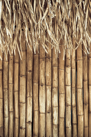 grunge bamboo background with straw roof.