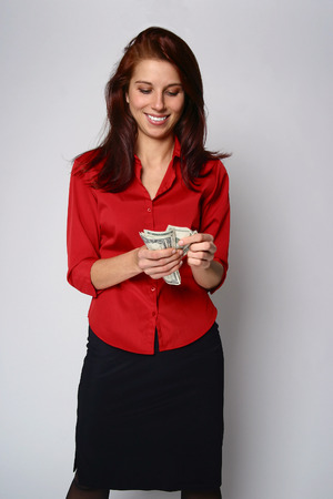 a young attractive woman in red blouse counting money Imagens