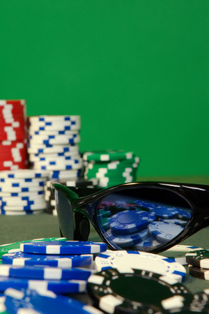 Poker table detail with playing chips and sunglasses