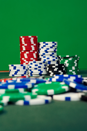 detail photo of stacked playing chips on green background