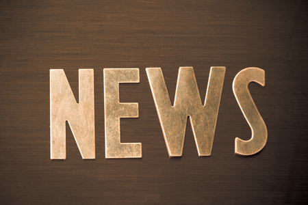 The word NEWS in copper colored letters on wood surface.