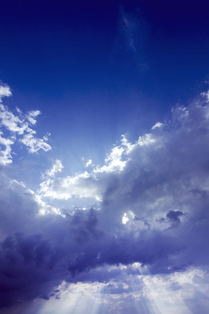 dramatic sky with light rays penetrating the clouds. Stock Photo