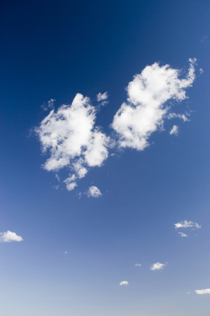 Scattered clouds on a clear blue sky Stock Photo