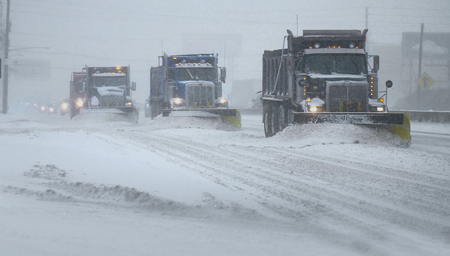 Snow Plows clearing a highway during a snow blizzard Foto de archivo