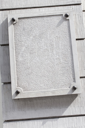 Blank white plaque with bolted frame and copy space for custom design.