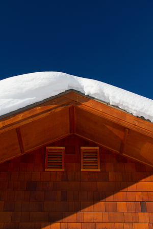 Detail of wooden log cabin with heavy snow on rooftop.