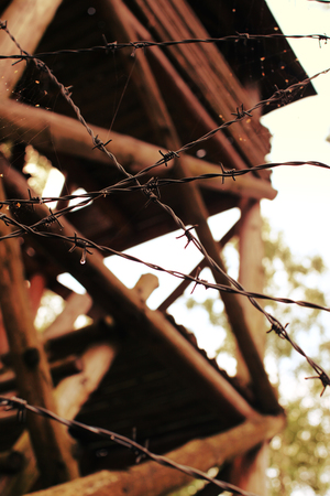 Detail of barbed wired fence and wooden watch tower.