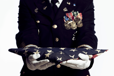 Army Soldier presenting folded USA flag. Focus on front of flag.