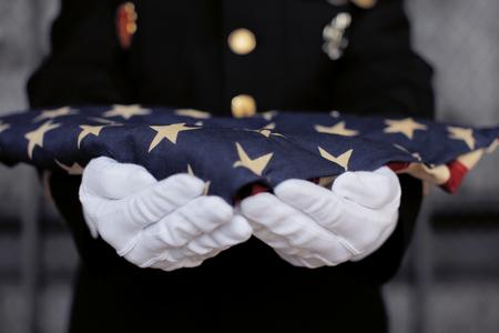 折りたたまれた米国旗を持つ軍人。
