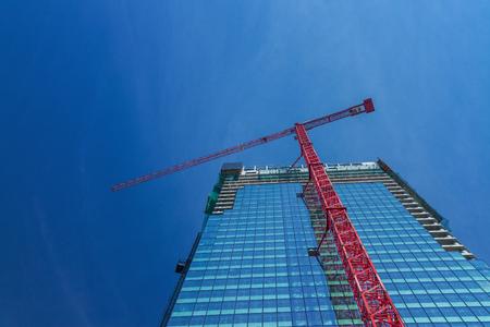 Heavy duty construction crane attached to a new skyscraper under development. Stock Photo