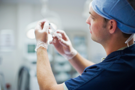 Medical Professional preparing a syringe. Stock Photo