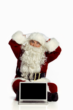 Santa Claus by a laptop, gesturing a suprised look.