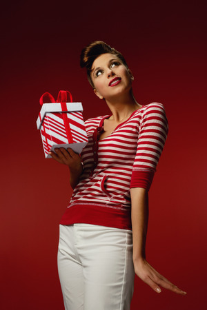 Retro styled woman wearing a red and white stripped shirt and holding a stripped present. Imagens