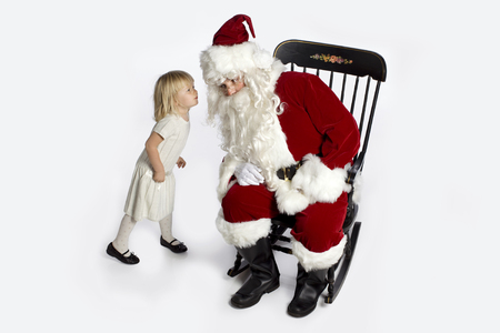 Little girl whispering into Santa's ear. Archivio Fotografico