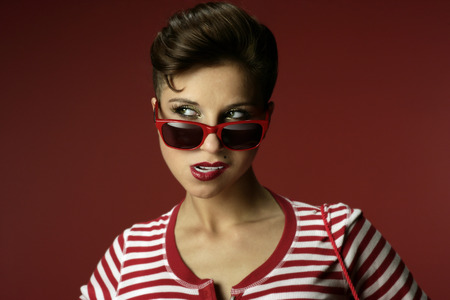 Brunette in red striped shirt with red background.